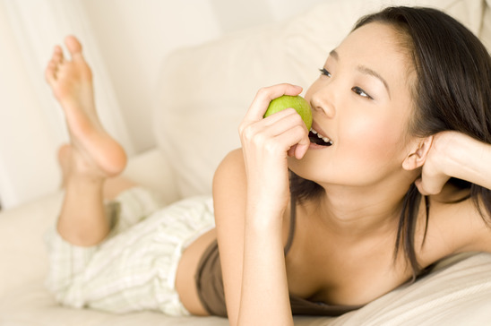 A beautiful young asian woman lying on the sofa at home eating a green apple