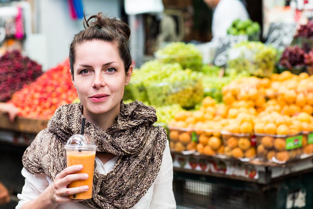Model holding an orange juice