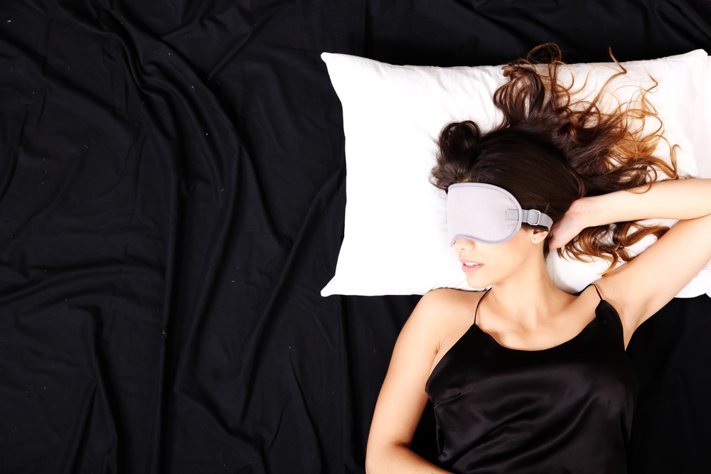 model laying on a bed with a face mask on