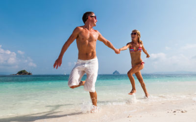 male and female couple prancing on the beach