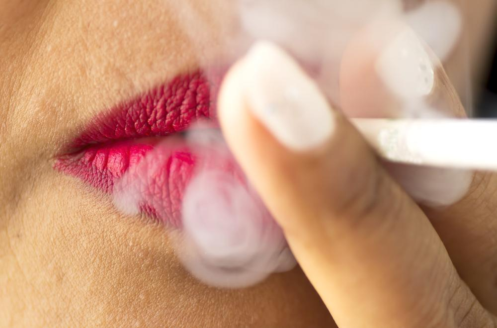 Woman with pink lipstick smoking