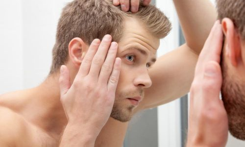 Male model looking in the mirror at his hair