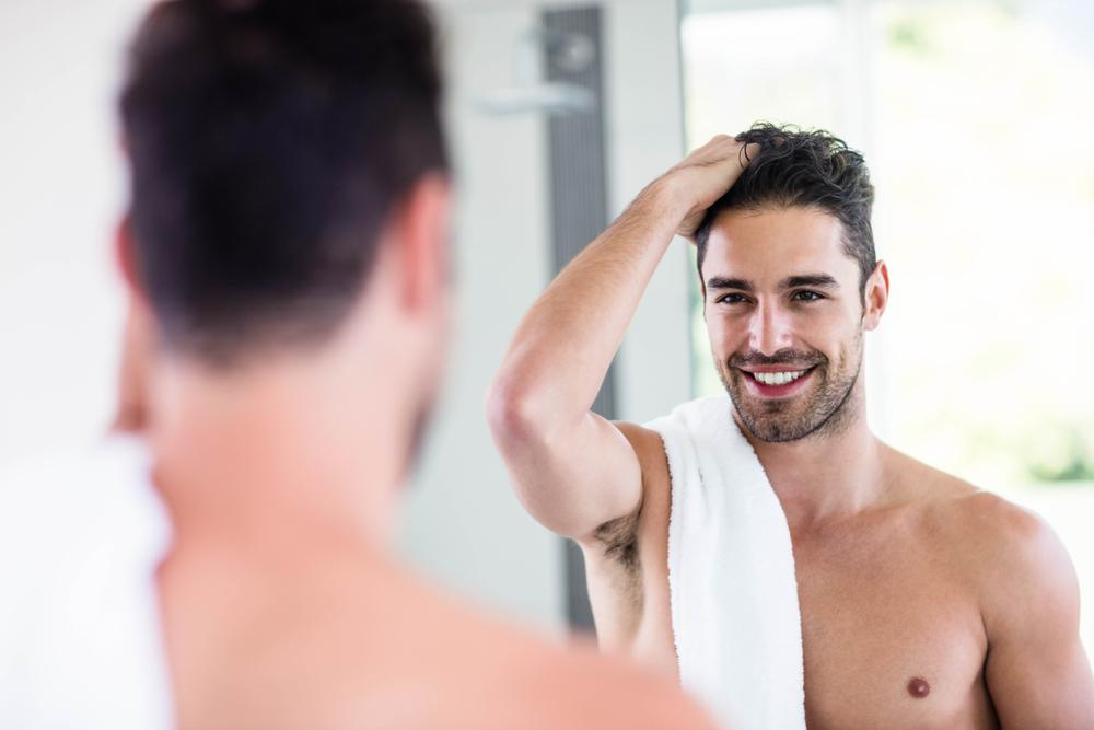 Male model looking at himself in the mirror shirtless