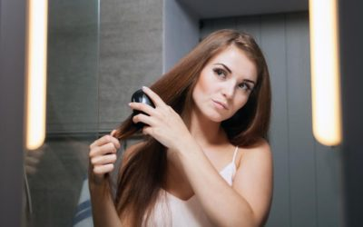Model blowdrying her hair in the mirror
