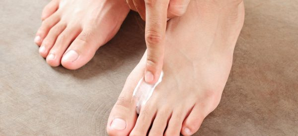 man applying athletes foot cream