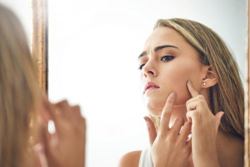 model trying to pop a pimple in the mirror