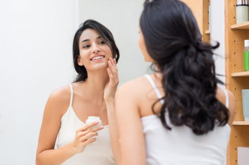Model putting on face cream in the mirror