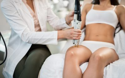 Tan woman sitting on table being treated for hair removal with medical laser.