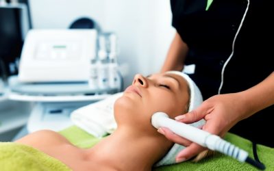 Tan woman laying down being treated with a laser for facials