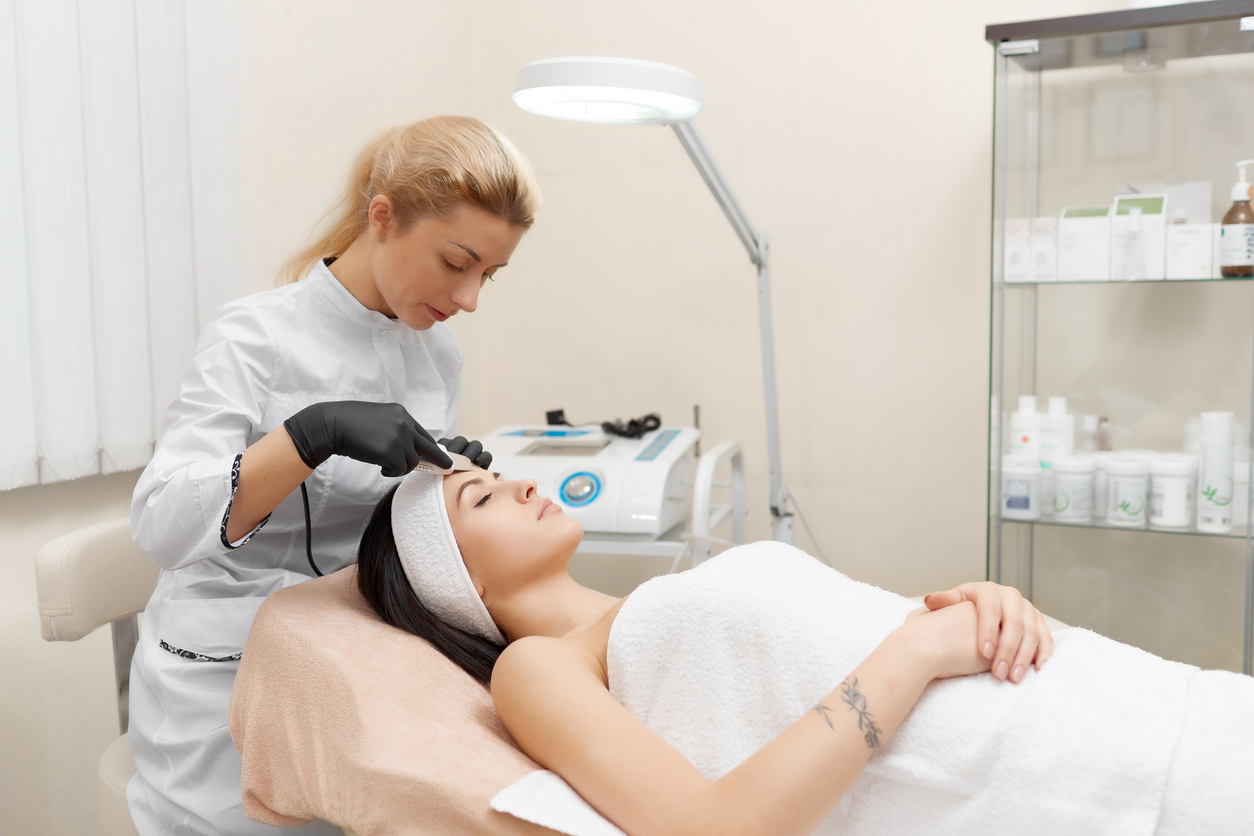 Cosmetologist doing procedure of ultrasonic cleaning of face. Young woman getting ultrasonic peeling in beauty salon