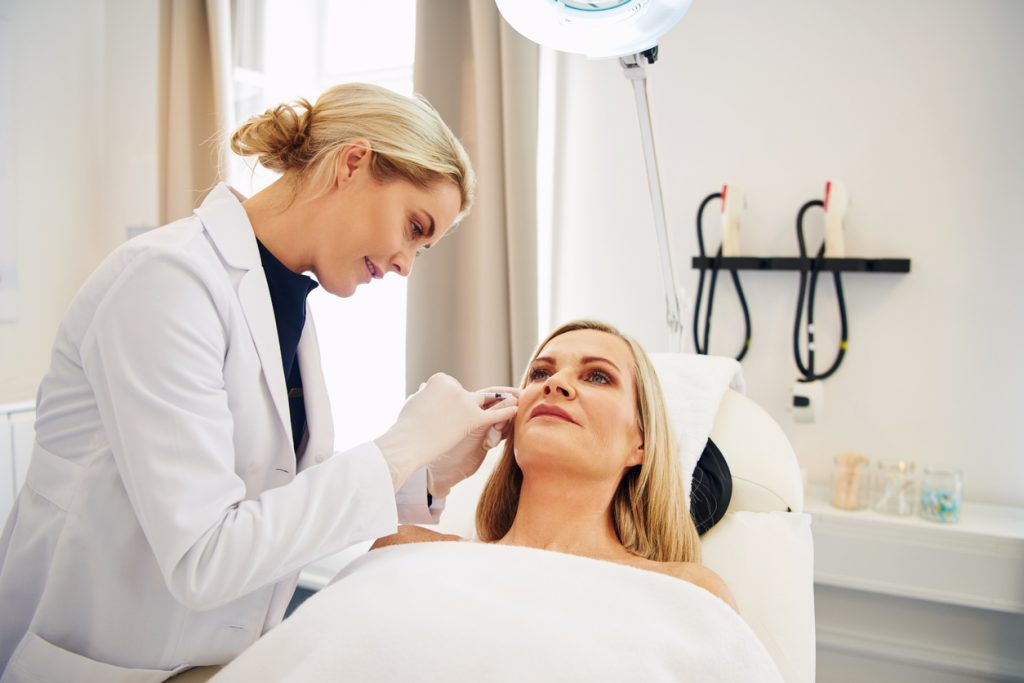 Young female doctor doing botox injections on the face of a mature woman lying on a table in a beauty clinic