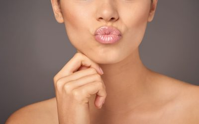 Closeup studio shot of a woman with gorgeous glossy lips against a gray background