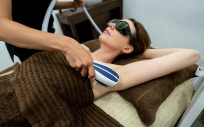 Beautiful woman at the spa getting a hair removal laser treatment in her armpits - beauty concepts