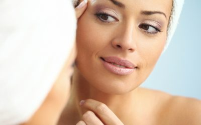Woman examining her skin in bathroom.