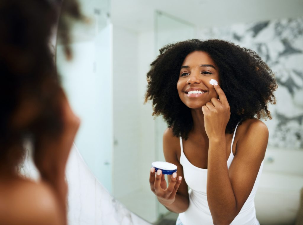 Shot of an attractive young woman applying moisturizer to her face at home