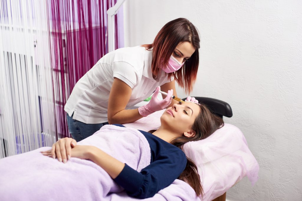 Filler injection for female forehead face. Plastic aesthetic facial surgery in beauty clinic. Beauty woman giving injections. Doctor in medical gloves and mask with syringe