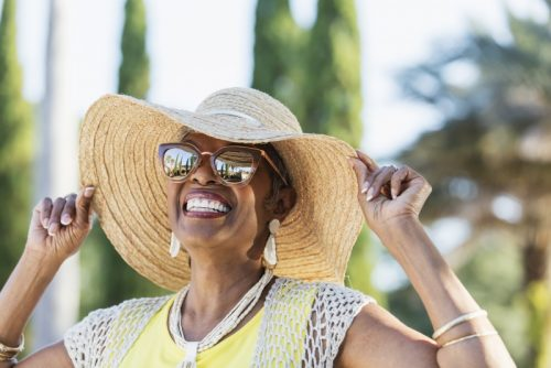 Woman outside smiling, wearing sunglasses and hat.