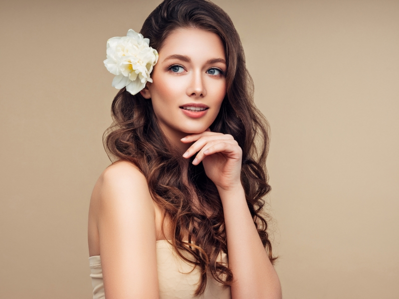 Girl with luscious hair and a flower in her hair.