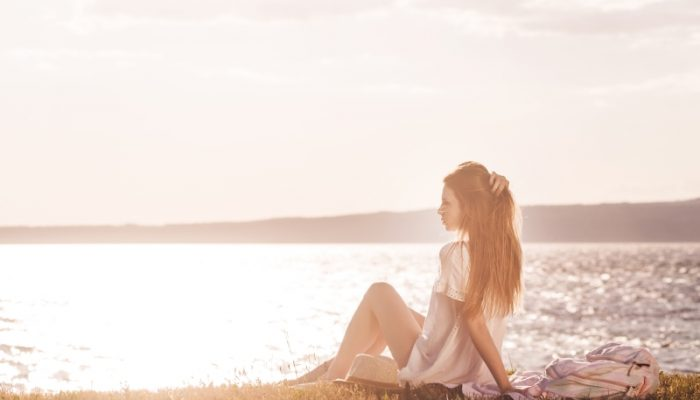 Young woman on the beach watching the sunset.